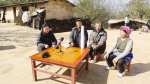 许鲜明教授(左一)到当地少数民族村寨采录原始语言材料。资料图片