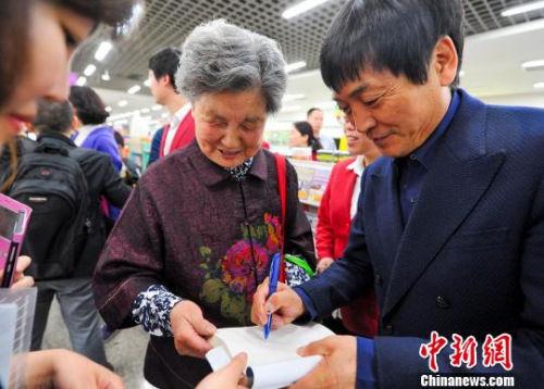 资料图:曹文轩为读者签名。 刘新 摄